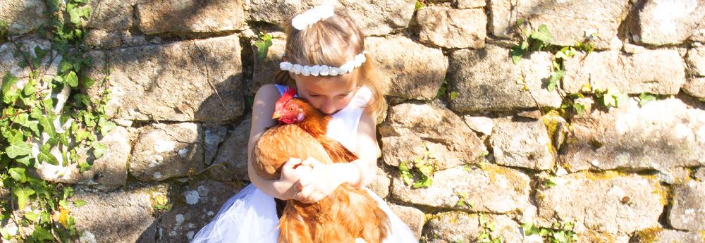 fille avec une robe et une couronne blanche tenant une poule